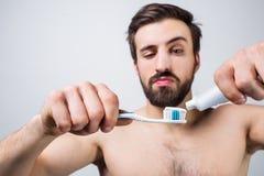Homem atrativo que põe alguma pasta de dente sobre sua escova de dentes Repete este tempo onde rotineiro diário do everu vem ao Fotografia de Stock Royalty Free