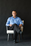 Homem atrativo que senta-se na cadeira no fundo escuro fotos de stock