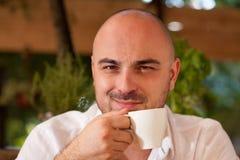 Homem atrativo que sorri ao guardar uma xícara de café Fotos de Stock Royalty Free
