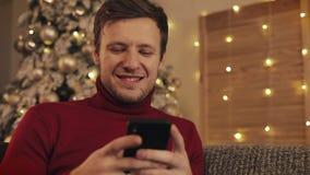 Homem atrativo que usa o smartphone que senta-se no sofá, mensagem, sorrindo no apartamento decorado perto de agradável Árvore de video estoque