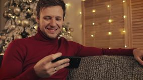 Homem atrativo que usa o smartphone que senta-se no sofá, mensagem, sorrindo no apartamento decorado perto de agradável Ele vídeo video estoque