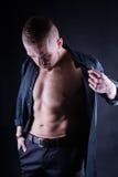 Homem atrativo, seguro, novo com a camisa aberta no torso muscular, Abs rasgado e CPE no fundo preto Imagem de Stock