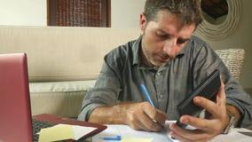 Homem autônomo atrativo novo com a calculadora e o portátil que fazem o documento explicando doméstico de pagamentos e de contas  video estoque