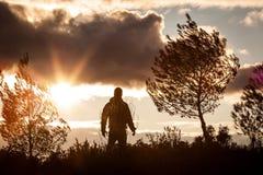Homem aventuroso observando um por do sol bonito na natureza, sozinho, stan Foto de Stock Royalty Free