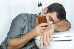 Homem bêbedo que dorme no toalete e que guardara uma garrafa fotografia de stock