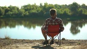 Homem bêbado que senta-se no banco de rio, admirando a vista e descansando, fim de semana da despesa video estoque