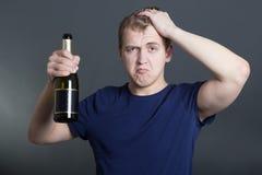 Homem bêbedo com a garrafa do champanhe sobre o cinza Fotos de Stock Royalty Free