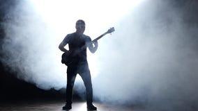 Homem baixo do guitarrista no fumo Movimento lento Fundo preto video estoque