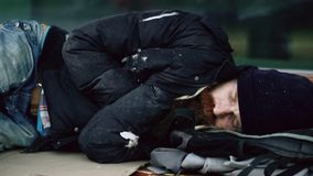 Homem bebido desabrigado novo que tenta dormir no cartão no banco no passeio imagens de stock