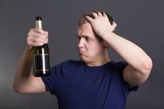 Homem bebido novo com a garrafa do champanhe sobre o cinza Foto de Stock Royalty Free