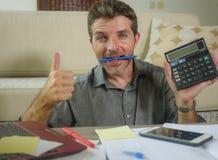 Homem bem sucedido considerável e feliz com a calculadora e o portátil que fazem a contabilidade doméstica e a renda de negócio m fotos de stock