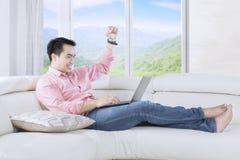 Homem bem sucedido que levanta a mão no sofá fotos de stock royalty free