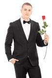 Homem bem vestido que guarda uma rosa vermelha foto de stock