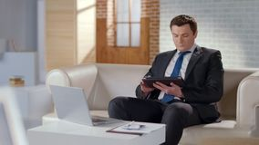 Homem bem vestido que usa a tabuleta no escritório, tecnologias modernas para controlar o negócio fotos de stock royalty free