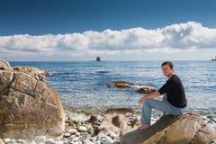 Homem bonito ativo que espera na praia Fotos de Stock Royalty Free