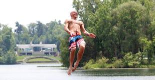 Homem bonito considerável que salta em um trampolim da água que flutua em um lago em Michigan durante o verão foto de stock royalty free