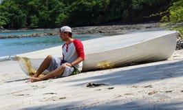 Homem bonito do naufrágio que senta-se na praia por uma ajuda de espera destruída do barco com oceano e selva no fundo imagem de stock