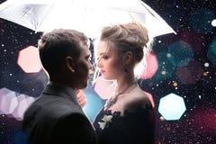 Homem bonito dos pares com a mulher com o guarda-chuva branco em luzes e em gotas instantâneas da chuva Fotografia de Stock Royalty Free