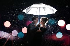 Homem bonito dos pares com a mulher com o guarda-chuva branco em luzes e em gotas instantâneas da chuva Foto de Stock