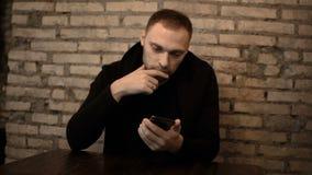 Homem bonito novo que senta-se no café perto da parede de tijolo e que usa o smartphone, surfando o Internet apenas filme