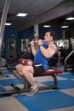 Homem bonito, poderoso, forte que levanta no gym Foto de Stock