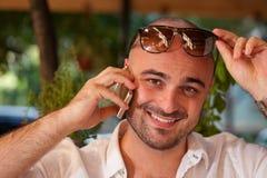 Homem bonito que sorri quando no telefone imagem de stock