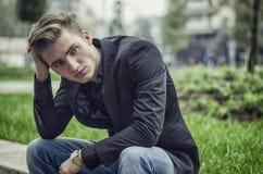 Homem branco novo deprimido que senta-se no lado da rua Imagens de Stock