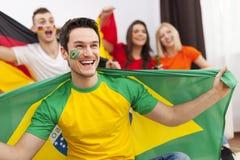 Homem brasileiro com seu cheering dos amigos Fotografia de Stock