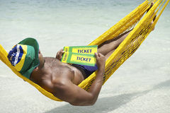 Homem brasileiro que relaxa com bilhetes de Brasil imagem de stock