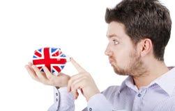 Homem britânico que joga com banco piggy Imagens de Stock Royalty Free