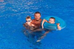 Homem bronzeado feliz com as duas crianças que nadam na associação exterior azul fotos de stock