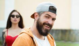 Homem brutal com barba e o bigode longos Forma da rua do moderno Indivíduo atrativo na frente da menina Seguro com o seu imagens de stock royalty free