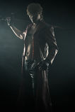 Homem brutal com uma espada isolada no preto Imagem de Stock