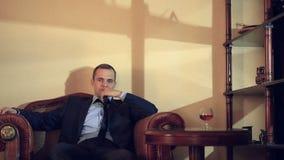 Homem brutal em um terno que senta-se em uma poltrona de couro, olhando na câmera e em gesticular Mãos na pessoa filme