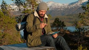 Homem brutal novo que olha um mapa em uma floresta no por do sol Tabela de madeira da floresta de Noruega para relaxar vídeos de arquivo