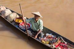 Homem burmese no barco de madeira longo pequeno que vende lembranças, trinkets e bijouterie no mercado de flutuação no lago Inle, Fotos de Stock