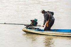 Homem burmese que segura o barco de motor caseiro no rio 3 Foto de Stock Royalty Free