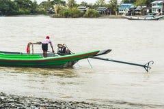 Homem burmese que segura o barco de motor caseiro no rio 3 Imagens de Stock