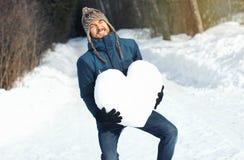 Homem cômico com a grande dificuldade que mantém o coração pesado enorme feito da neve, no parque do inverno Declarações do amor, imagens de stock royalty free
