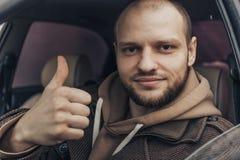 Homem calmo de sorriso que senta-se dentro do carro que mostra os polegares acima Pessoa positiva do motorista fotografia de stock