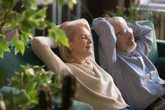 Homem calmo e mulher envelhecidos médios que relaxam no sofá confortável imagens de stock