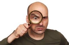 Homem calvo chocado que olha através da lupa fotografia de stock royalty free