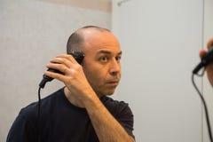 Homem calvo com a camisa preta que barbeia seu cabelo com lâmina elétrica na frente de um espelho Fotos de Stock Royalty Free