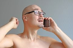 Homem calvo considerável novo em vidros pretos que fala no telefone Retrato do close up de um homem Más notícias, tristeza, probl fotos de stock royalty free