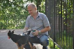 Homem calvo de sorriso com cão fotografia de stock