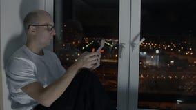 Homem calvo nos vidros que olham o PC da tabuleta que senta-se na soleira com arquitetura da cidade da noite filme