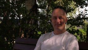 Homem calvo positivo que olha a câmera e que sorri ao sentar-se no banco fora filme