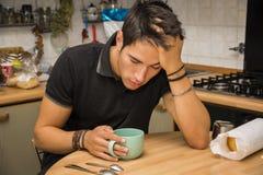 Homem cansado com o café que senta-se na mesa de cozinha fotos de stock