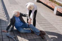 Homem cansado do envelhecimento que cai para baixo na estrada Foto de Stock Royalty Free