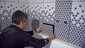 Homem cansado do trabalhador do tiler para instalar a última telha no banheiro vídeos de arquivo